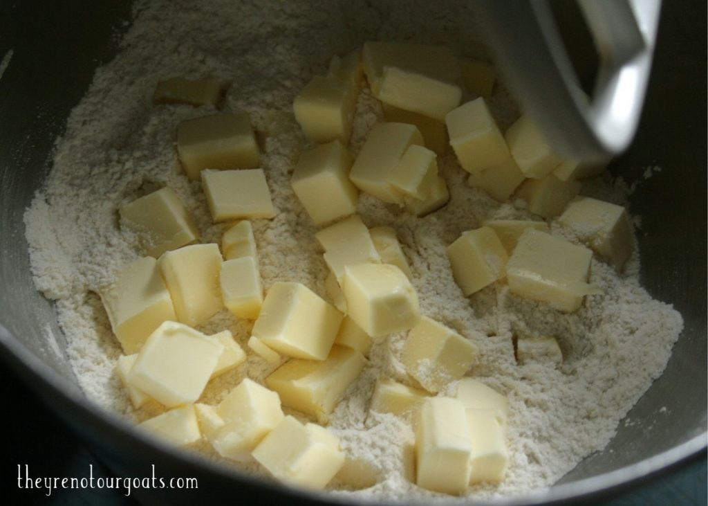 Small cubes of butter resting in a mixing bowl on top of a mixture of flour, sugar, and salt.