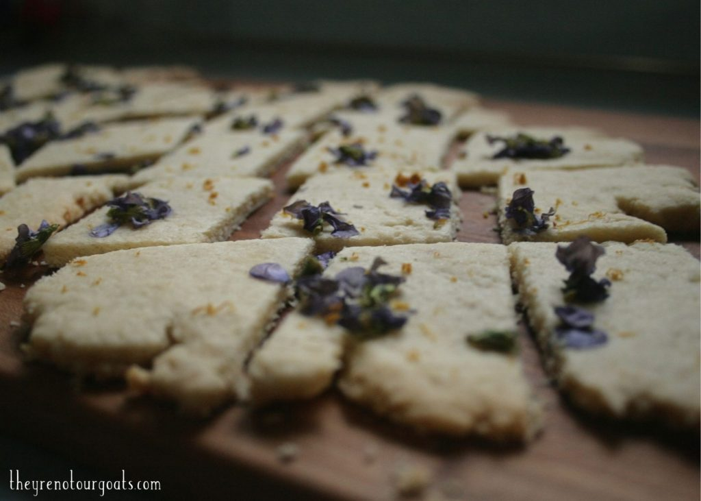 Close up of lemon violet shortbread cookies on top of a cutting board