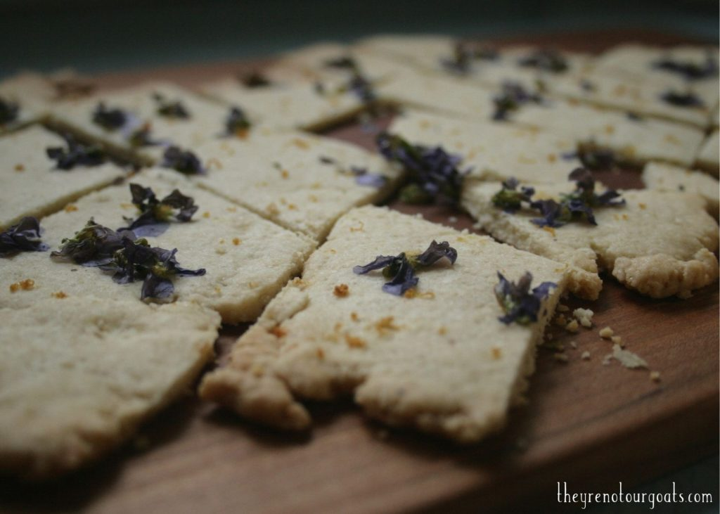 Lemon violet shortbread cookies sitting on top of a cutting board.